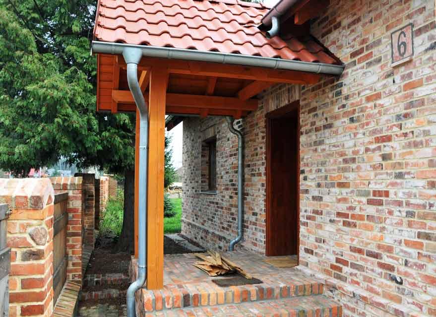 Fassade und Zaun aus historischen Ziegelsteinen gemauert.